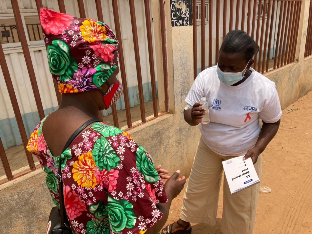 Claudine orienta mulher refugiada de sua comunidade para a prevenção à COVID-19.